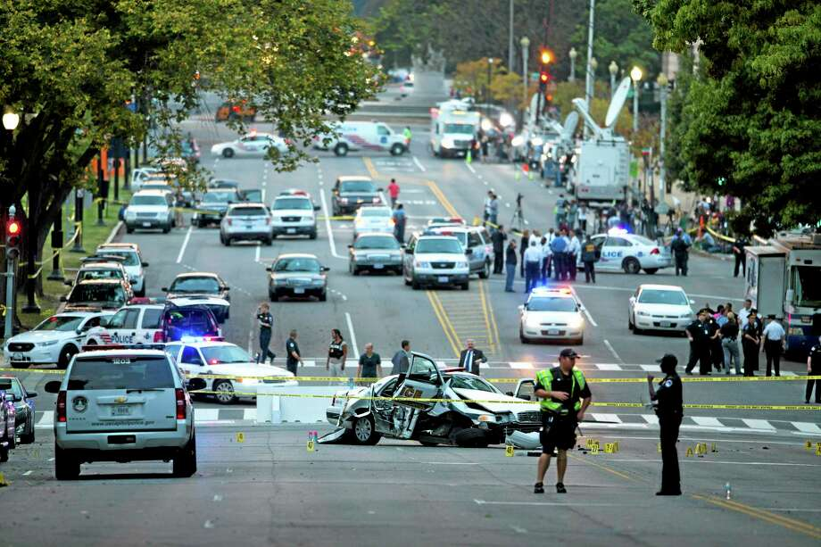 A damaged Capitol Hill police car is surrounded by crime scene tape on Constitution Avenue near the U.S. Capitol after a car chase and shooting Thursday, Oct. 3, 2013, in Washington. A woman with a young child inside tried to ram through a White House barricade, then led police on a chase toward the Capitol, where police shot and killed her, witnesses and officials said. (AP Photo/ Evan Vucci) Photo: AP / AP