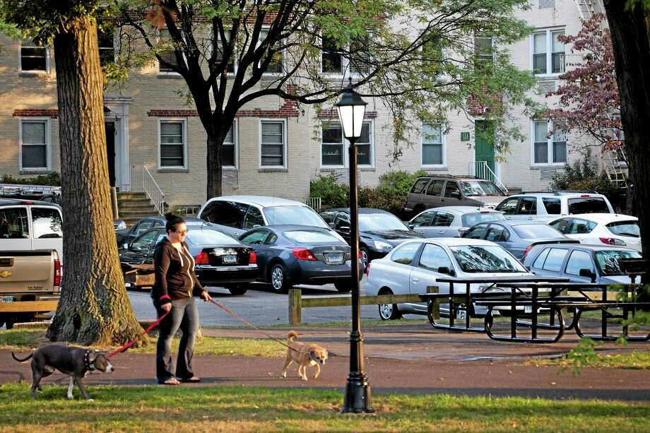 A dog-walker passes outside the apartment complex where Miriam Carey is believed to have lived in Stamford, Conn., Friday, Oct. 4, 2013. Law-enforcement authorities have identified Carey, 34, as the woman who, with a 1-year-old child in her car, led Secret Service and police on a harrowing chase in Washington from the White House past the Capitol Thursday, attempting to penetrate the security barriers at both national landmarks before she was shot to death, police said.  The child avoided serious injury and was taken into protective custody.  (AP Photo/John Minchillo) Photo: AP / FR170537 AP