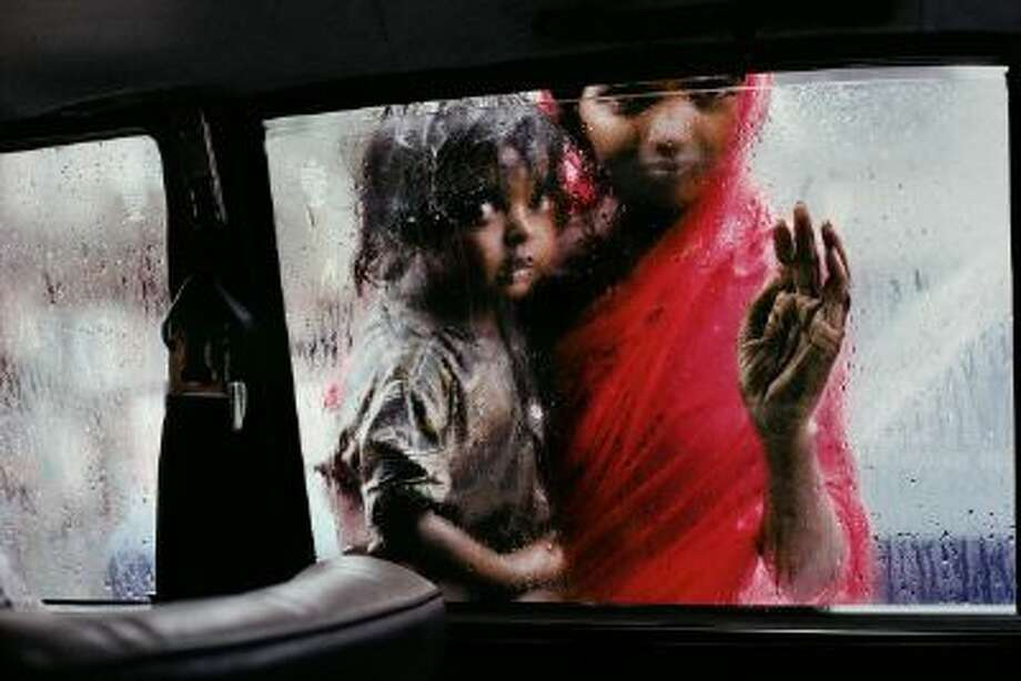 An all-too-common sight on the streets of Bombay, a destitute woman and child make a squalid living by begging. Fully half of the booming city's 13 million people were living on the streets or in tin-and-cardboard shacks. Perhaps 600,000 of them were crammed into a one-square-mile slum called Dharavi - the biggest slum in Asia. The city is now called Mumbai.