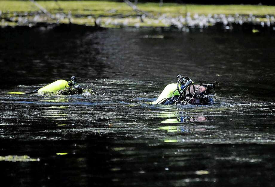 Members of the Connecticut State Police Dive Team searches Pine Lake in Bristol, Conn., on  Tuesday, Aug. 6, 2013, the hometown of the former New England Patriots football player Aaron Hernandez. The divers searched the lake for a second week. Hernandez has pleaded not guilty to murder in the death of Odin Lloyd, a 27-year-old Boston semi-professional football player.  (AP Photo/Bristol Press, Mike Orazzi) Photo: AP / Bristol Press