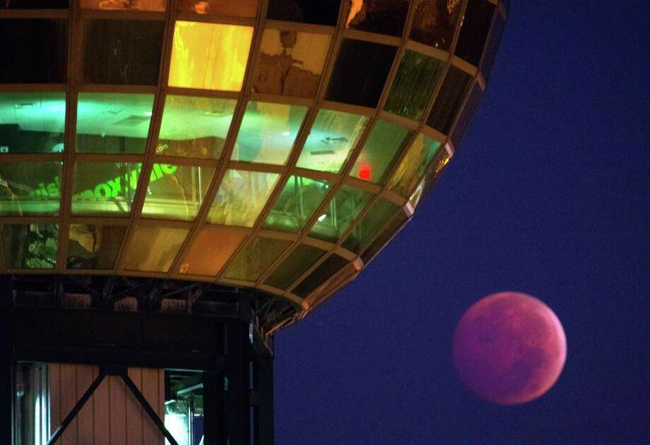 """The Earth's shadow is cast over the moon during a total lunar eclipse, as seen from beneath the Sunsphere in Knoxville, Tenn. Wednesday, Oct. 8, 2014. The red hue results from sunlight scattering off Earth's atmosphere, in what is known as a """"blood moon."""" (AP Photo/Knoxville News Sentinel, Adam Lau) Photo: AP / Knoxville News Sentinel"""