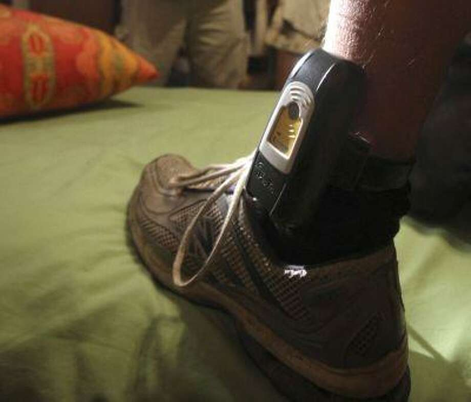 In this Aug. 3, 2009, file photo, Parole Agent Steve Nakamura uses a flashlight to inspect a GPS locater worn on the ankle of a parolee in Rio Linda, Calif. Photo: AP / AP
