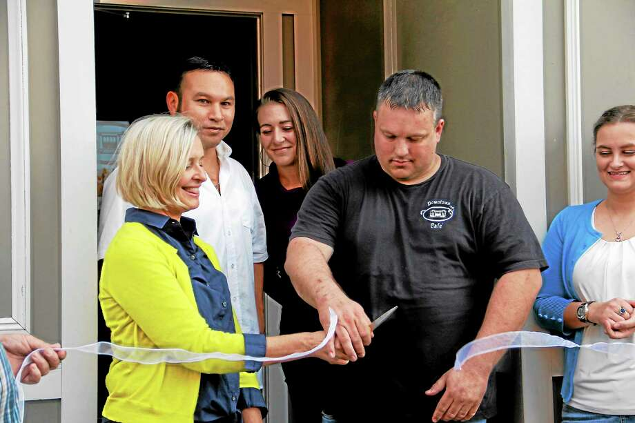 From left: Director of Economic Development for the city Rose Ponte helps Paul Murdock cut a ribbon for the grand opening of the Downtown Café on Water Street on Friday, Oct. 4, in Torrington as his business partner, David Haberfeld, and others look on. Photo: Photos By Esteban L. Hernandez—Register Citizen
