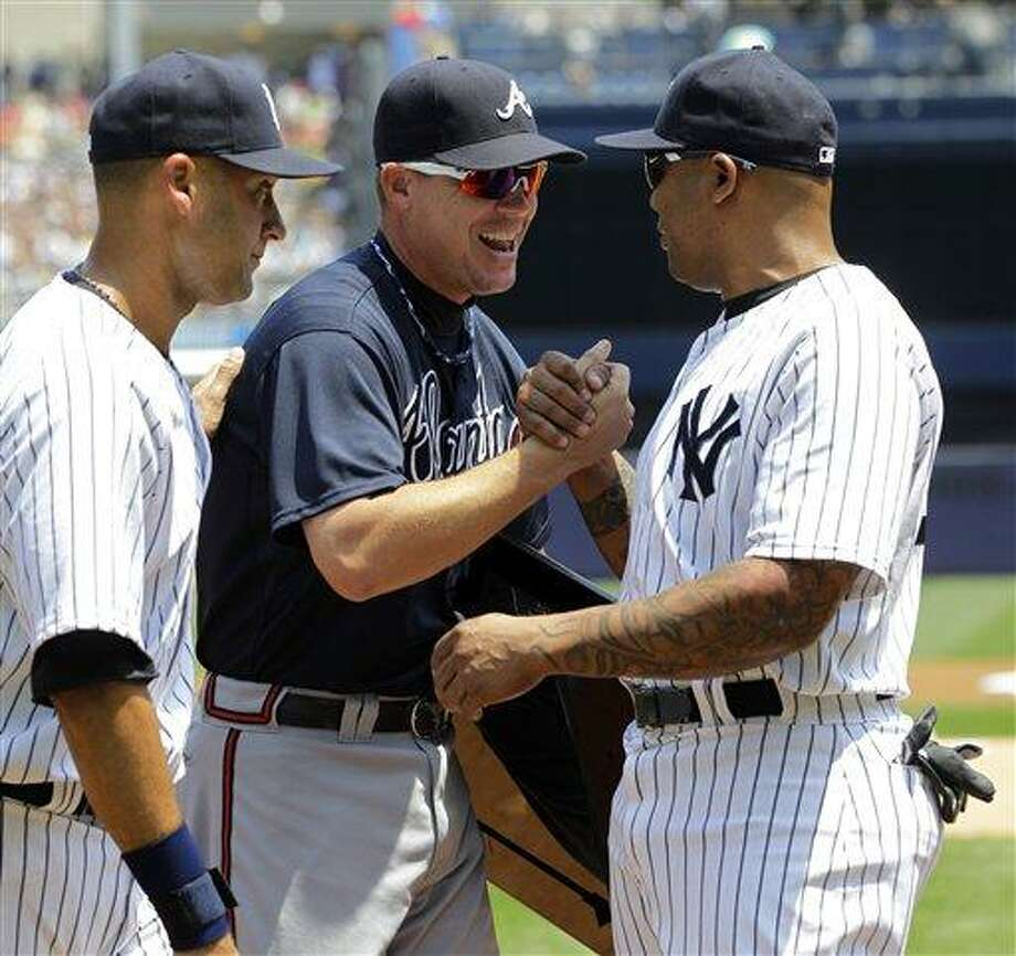 New York Yankees' Derek Jeter, left, watches as New York Yankees' Andruw Jones, right, congratulates Atlanta Braves' Chipper Jones, after presenting him with third base from Tuesday night's game,  before the two teams faced off in a baseball game at Yankee Stadium in New York, Wednesday, June 20, 2012.  Jones is retiring at the end of the season. (AP Photo/Kathy Willens) Photo: ASSOCIATED PRESS / AP2012