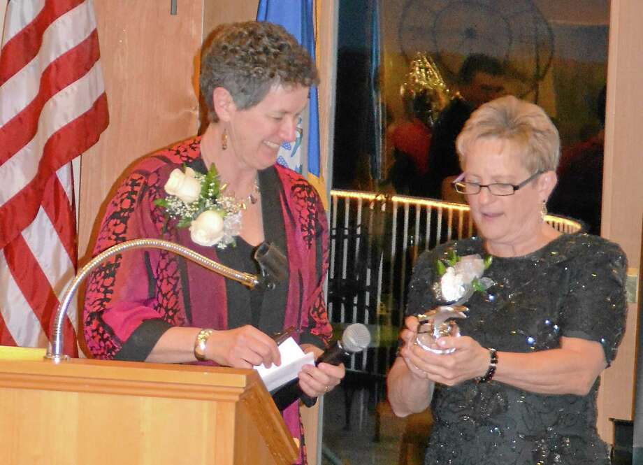 Kate Hartman/Register Citizen -- Barbara Spiegel, executive director of the Susan B. Anthony Project, left, accepts an on behalf of her staff from Gail Olsen during the United Way of Northwest Connecticutís inaugural Womenís Initiative Gala. Photo: Journal Register Co.