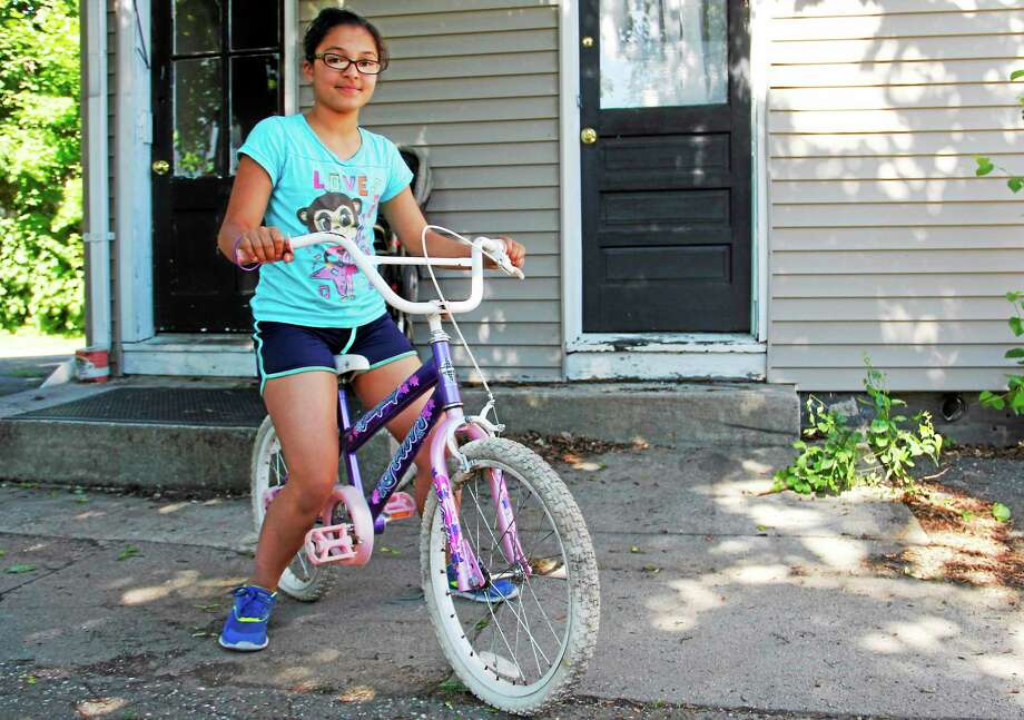Emma Mabe, 10, sits on a bike donated by a Torrington Police Officer. The girl's bike had been stolen a few weeks back, and the officer made an effort to find a replacement. Photo: Esteban L. Hernandez — The Register Citizen