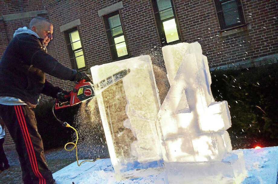 Rob Ferrucci carves blocks of ice into numerals 2014 at the armory in Torrington for the city's Last Night celebration. Photo: John Berry — The Register Citizen