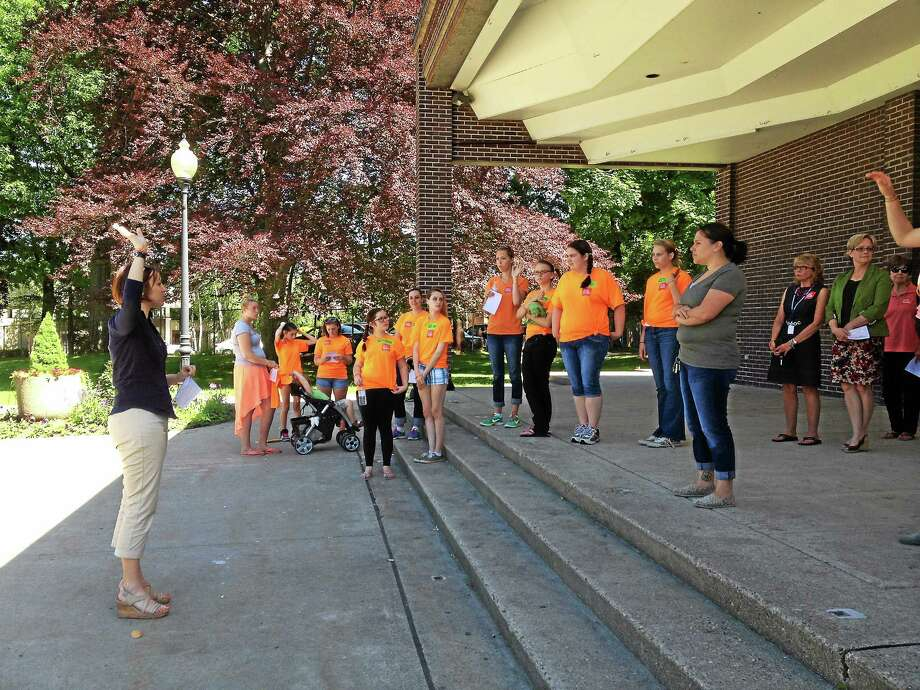 Dawn Crayco (left), deputy director of End Hunger Connecticut talks to volunteers before splitting them into groups to canvas the area to spread the word about the summer meal program. In the orange shirts are the volunteers from Explorations School. Photo: Jenny Golfin — The Register Citizen