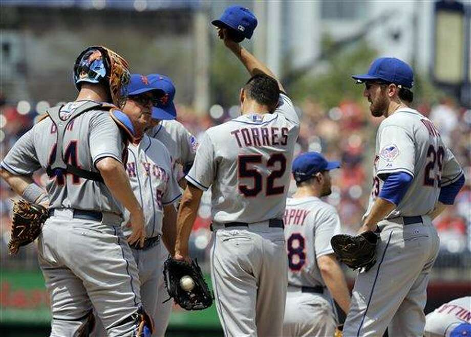 New York Mets pitching coach Dan Warthen (59), second from left, talks with New York Mets starting pitcher Carlos Torres (52) during a baseball game against the Washington Nationals at Nationals Park Sunday, July 28, 2013, in Washington. (AP Photo/Alex Brandon) Photo: AP / AP