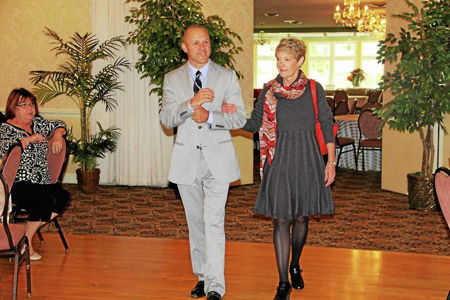 Brian Mattiello, vice president of organizational development at Charlotte Hungerford Hospital escorts one of the models during the hospital auxiliary's 30th annual fashion show in Torrington Wednesday. Photo: Anita Garnett — Special To The Register Citizen