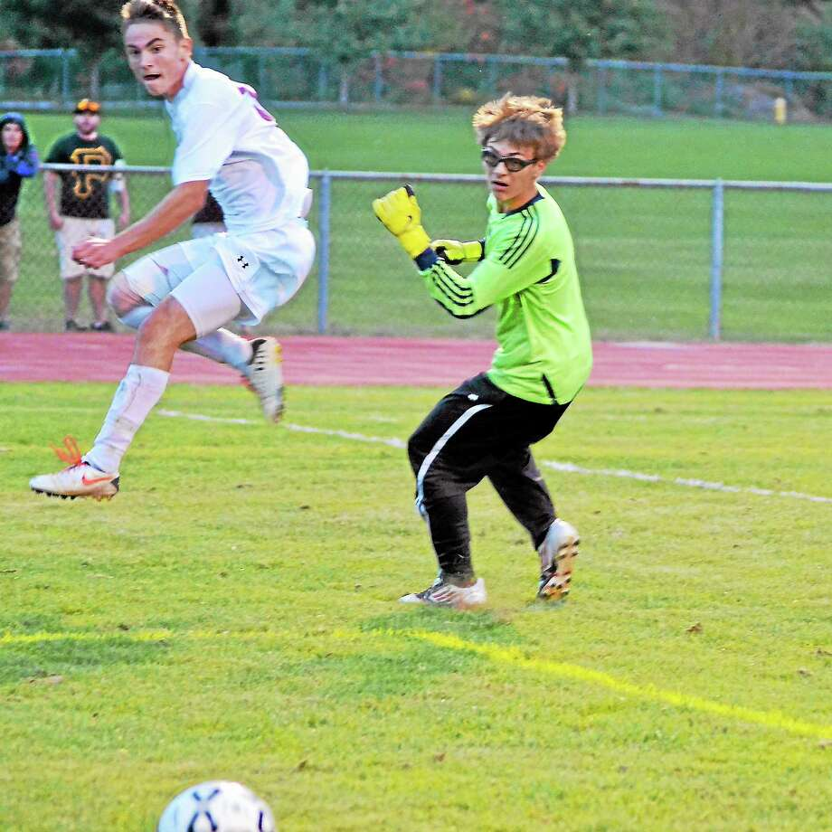 Amar Suljic shoots the ball past Sacred Heart goaltender Cameron Hintz for his second goal of the game. Suljic scored a hat-trick in Torrington's 6-0 win over Sacred Heart. Photo: Pete Paguaga — Register Citizen