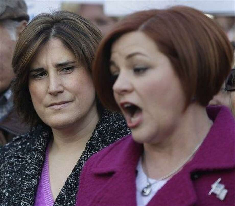 While New York City Council speaker and mayoral hopeful Christine Quinn, right, speaks to the media as her wife Kim Catullo looks on in New York, Sunday, March 10, 2013. The New York City Council speaker has formally launched what she hopes will be a history-making mayoral bid this fall. (AP Photo/Seth Wenig) Photo: AP / AP