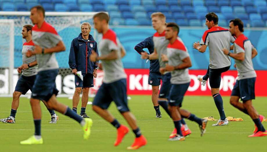 United States' head coach Jurgen Klinsmann, back left, looks on as his team warms up during an official training session Sunday in Brazil. Photo: Julio Cortez — The Associated Press  / AP