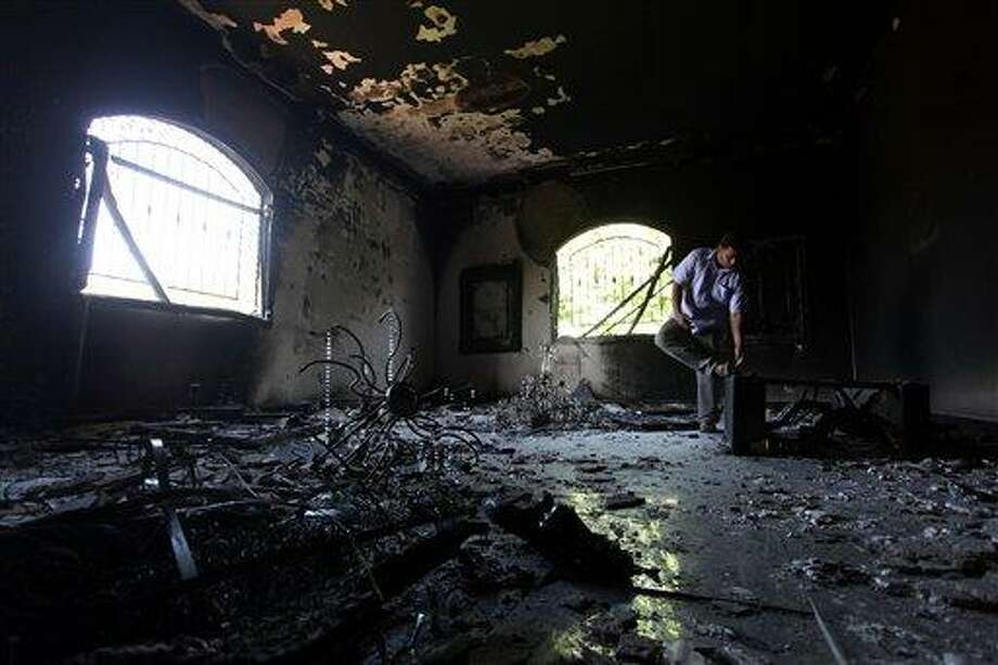 FILE - In this Thursday, Sept. 13, 2012 file photo, a Libyan man investigates the inside of the U.S. Consulate after an attack that killed four Americans, including Ambassador Chris Stevens, on the night of Tuesday, Sept. 11, 2012, in Benghazi, Libya.  House Republicans proposed slashing billions of dollars in U.S. diplomacy and overseas aid programs Thursday, July 18, 2013, in legislation that will face fierce opposition from the Obama administration and the Democratic-led Senate. The House Appropriations Committee's 2014 foreign operations bill would give full funding to embassy security, with the goal of preventing a repeat of last year's deadly attack in Benghazi, Libya. The measure also would maintain security money for allies Israel and Jordan.(AP Photo/Mohammad Hannon, File) Photo: AP / AP