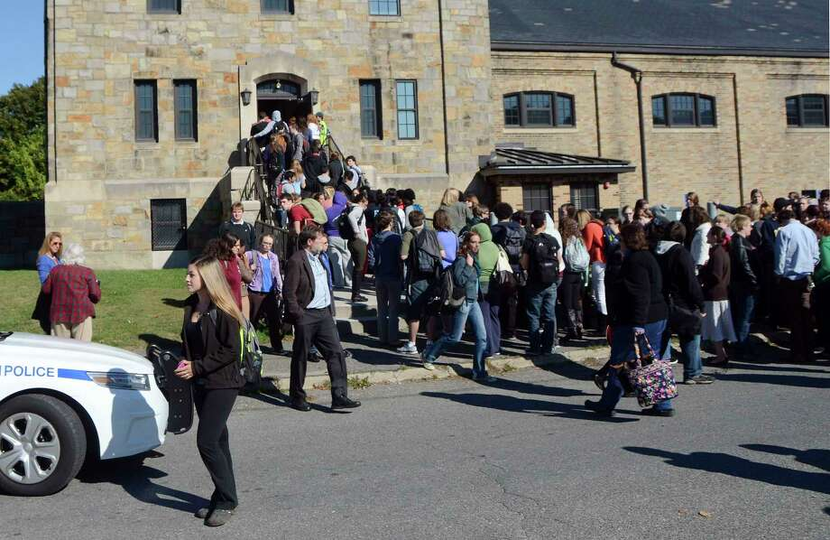 In this Monday, Oct. 6, 2014 photo, Massachusetts College of Liberal Arts students, faculty and staff are evacuated into the armory in North Adams, Mass., following a bomb threat on campus. Photo: Gillian Jones — The Berkshire Eagle  / The Berkshire Eagle
