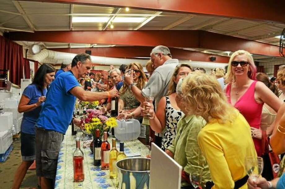 Wine lovers gather around to sample from a variety of local vineyards during the fifth-annual Connecticut Wine Festival in Goshen on Saturday. (Kate Hartman-Register Citizen)