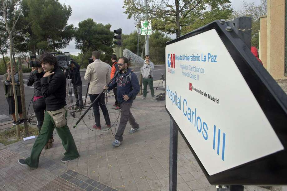 Journalists work at the entrance of the Carlos III  hospital in Madrid, Spain, Tuesday, Oct. 7, 2014 where a Spanish nurse who is believed to have contracted the ebola virus from a 69-year-old Spanish priest is being treated after testing positive for the virus. Raising fresh concern around the world, the nurse in Spain became the first person known to catch Ebola outside the outbreak zone in West Africa. In Spain, the stricken nurse had been part of a team that treated two missionaries flown home to Spain after becoming infected with Ebola in West Africa. The nurse's only symptom was a fever, but the infection was confirmed by two tests, Spanish health officials said. She was being treated in isolation, while authorities drew up a list of people she had had contact with. (AP Photo/Paul White) Photo: AP / AP