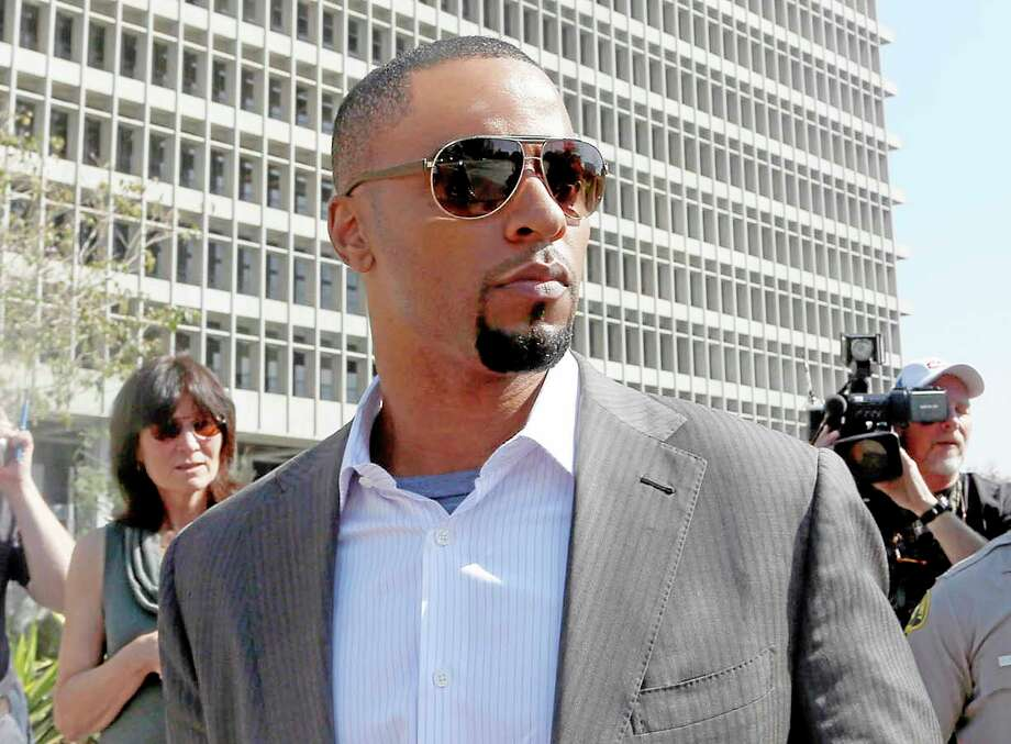 Former NFL safety Darren Sharper has turned himself in to police in Los Angeles. An arrest warrant was issued for Sharper and another man, accusing them of raping two women in New Orleans last year. Sharper also is under investigation in sexual assault cases in Florida, Nevada and Arizona and has pleaded not guilty to rape charges in Los Angeles. Photo: Nick Ut — The Associated Press  / AP