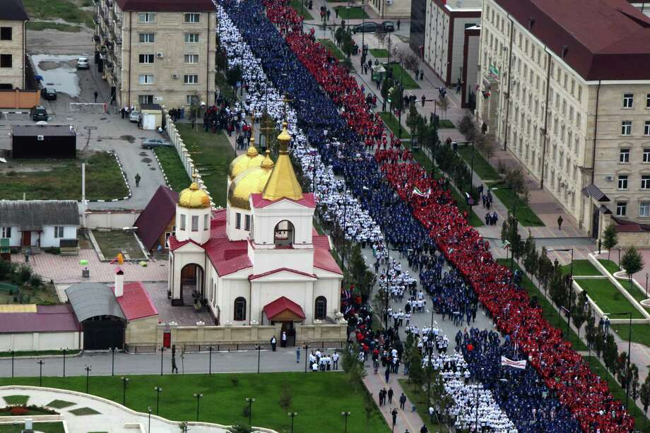 People dressed in colors of Russian flag march in Grozny, Russia, Tuesday, Oct. 7, 2014. In the Chechen capital of Grozny, thousands gathered to form a 600-meter long Russian flag through the streets. Russian President Vladimir Putin is celebrating his 62nd birthday in the wilderness of Siberia, as supporters from across Russia create tributes in his honor. (AP Photo/ Musa Sadulayev) Photo: AP / AP