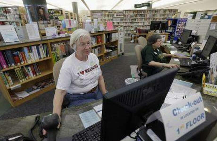 Librarian Joan Limbert, left, works at her station inside the Barbara Bush Branch Library Friday, June 28, 2013, in Spring, Texas. The nation's librarians will be recruited to help people get signed up for insurance under President Barack Obama's health care overhaul. Up to 17,000 U.S. libraries will be part of the effort to get information and crucial computer time to the millions of uninsured Americans who need to get coverage under the law. The undertaking will be announced Sunday in Chicago at the annual conference of the American Library Association, according to federal officials who released the information early to The Associated Press. (AP Photo/David J. Phillip) Photo: AP / AP