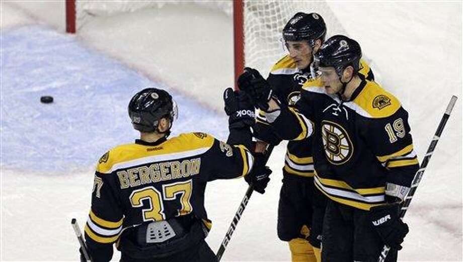 Boston Bruins center Tyler Seguin (19) is congratulated by Patrice Bergeron (37) and Brad Marchand, rear right, after his empty-net goal against the Toronto Maple Leafs during the third period of an NHL hockey game in Boston, Thursday, March 7, 2013. (AP Photo/Charles Krupa) Photo: ASSOCIATED PRESS / AP2013