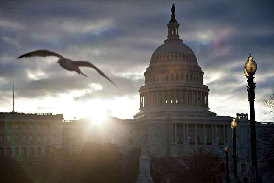 At dawn, the sun breaks through dark clouds over Capitol Hill in Washington, Thursday, March 7, 2013. (AP Photo/J. Scott Applewhite) Photo: ASSOCIATED PRESS / AP2013