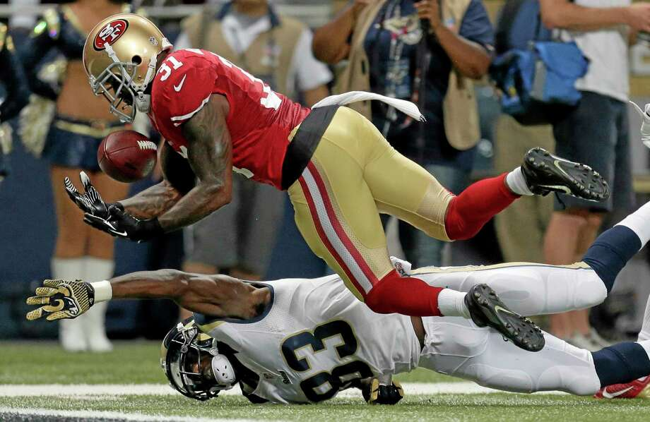 San Francisco 49ers safety Donte Whitner, top, intercepts a pass over Rams wide receiver Brian Quick during the second quarter of Thursday's game in St. Louis. Photo: Charlie Riedel — The Associated Press  / AP