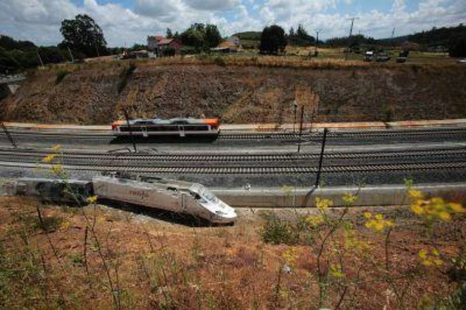 A passenger train passes by a wrecked train engine at the site of a train crash in Santiago de Compostela, northwestern Spain, July 26, 2013. Photo: REUTERS / X01219