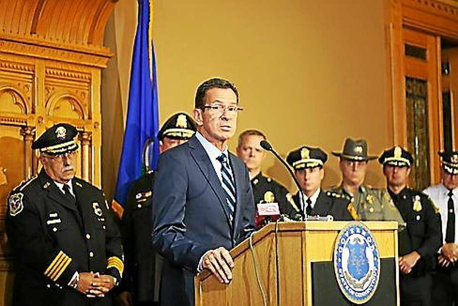 Gov. Dannel P. Malloy announces the findings of the state's annual crime report. Law enforcement officials from around the state stand behind him. Photo: Hugh McQuaid — CTNewsJunkie.com