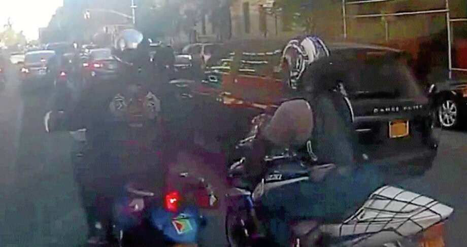 In this frame grab from video provided by the New York Police Department, motorcyclists ride alongside a sport utility vehicle, Sunday, Sept. 29, 2013, in New York. Police say that a man driving with his family along a New York City highway was attacked and beaten by a large group of motorcyclists who first surrounded his sport utility vehicle and stopped it on the road, then chased him for miles after he plowed through the blockade of bikes in an attempt to escape. (AP Photo/New York Police Department) Photo: AP / New York Police Department