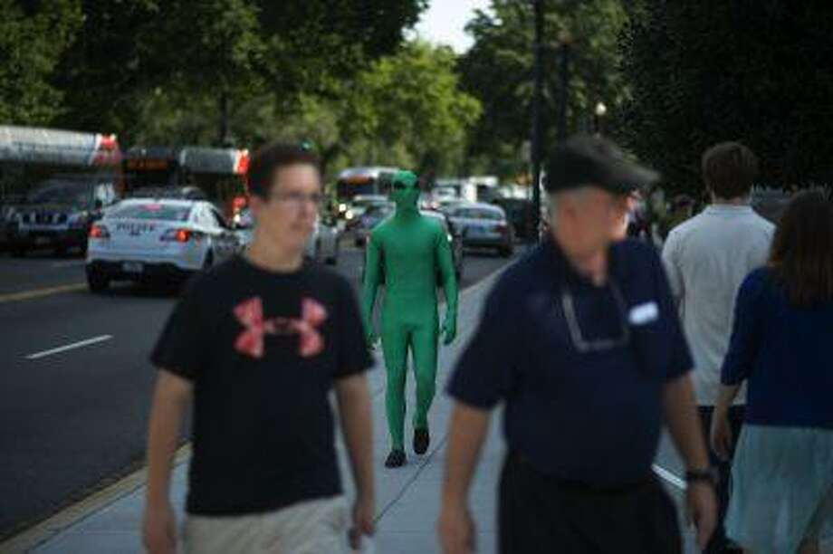 "Colin Best, center, dresses as an alien as he takes part in a scavenger hunt Wednesday in Washington as part of ""The Alien's Guide to the Ruins of Washington D.C."" exhibit by the Corcoran Gallery of Art. Photo: The Washington Post / The Washington Post"