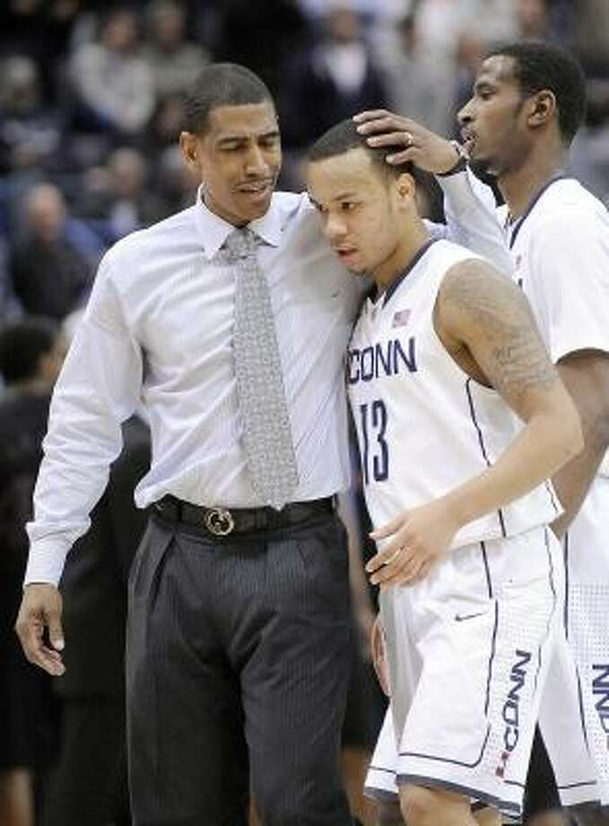 Connecticut coach Kevin Ollie speaks with Shabazz Napier late in overtime of Connecticut's 73-66 victory over Cincinnati in an NCAA college basketball game in Hartford, Conn., Thursday, Feb. 21, 2013. (AP Photo/Fred Beckham) Photo: ASSOCIATED PRESS / AP2013