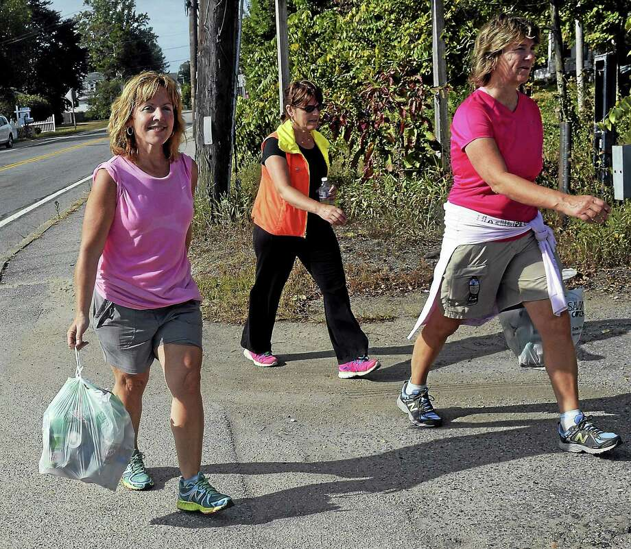 In this Sept. 21, 2014 photo, Deb McGowan of North Stonington, Conn., left, walks along U.S. Route 3 while picking up recyclables with friends Tracy Stedman, center, Linda Stefanski, right, in Ashaway, R.I., Over the past year, McGowan, 47, has redeemed 10,000 beverage containers to raise her $500 fundraising commitment for the ninth annual Terri Brodeur Breast Cancer Foundation Walk Across Southeastern Connecticut. Photo: AP Photo/The Day, Tim Martin  / The Day