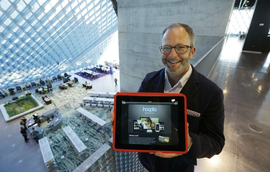 In this Sept. 11, 2013 photo, Kirk Blankenship, Electronic Resources Librarian for Seattle Public Libraries, poses for a photo as he holds a tablet with the website for streaming-media company Hoopla, which the library is using to offer patrons free access to streaming movies, music, and audiobooks. (AP Photo/Ted S. Warren) Photo: AP / AP