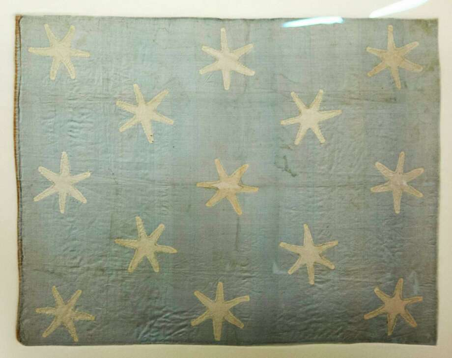 In this Thursday, June 5, 2014 photo shown is the recently conserved George Washington's flag, which flew to denote his presence at various battles during the war against Britain, at the Museum of the American Revolution's facility near Philadelphia. The small banner, now a faded blue with 13 white six-pointed stars, is among thousands of objects waiting for a permanent home at the soon-to-be-built Revolution museum.  (AP Photo/Matt Rourke) Photo: AP / AP