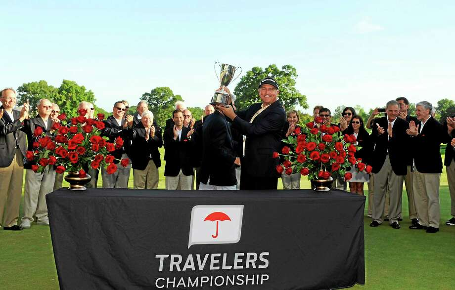 Ken Duke raises the trophy after winning the 2013 Travelers Championship last June in Cromwell. A 10-year title sponsorship extension for the Travelers Championship was announced on Thursday. Photo: Fred Beckham — The Associated Press  / FR153656 AP