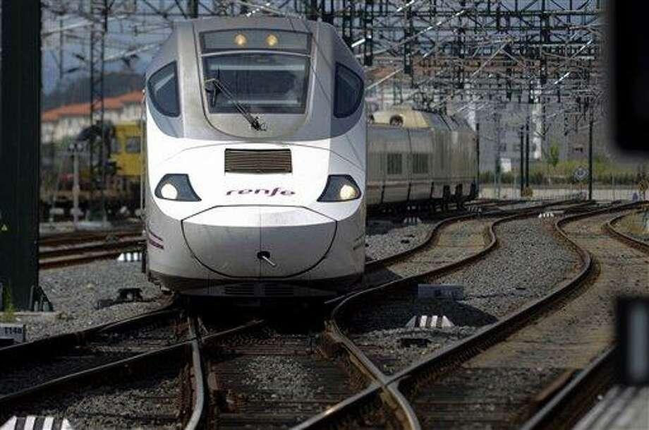 """A passenger 'Alvia' type train pulls into the station in Santiago de Compostela, Spain, Friday July 26, 2013. The 'Alvia' train, the same as the one that crashed Wednesday is the first to operate on this line after the accident. Investigators have taken possession of the """"black boxes"""" of the Spain train that hurtled at high-speed along a curve and derailed, killing 80 people, a court official said Friday. Analysis will be performed to determine why the train was traveling far above the speed limit when it crashed near a station in Santiago de Compostela, in the northwestern Galicia region, said court spokeswoman Maria Pardo Rios. The train's operator remained hospitalised Friday and will be questioned by police but she said the interview will not happen Friday. (AP Photo/Brais Lorenzo) Photo: AP / AP"""