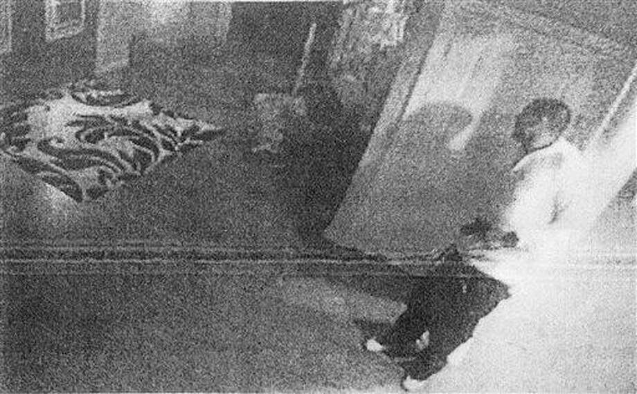 This black and white photo taken from former New England Patriot Aaron Hernandez's home surveillance system in North Attleborough, Mass., and released in documents by the Attleboro District Court Thursday, July 25, 2013, shows Hernandez holding what authorities said appears to be a gun, shortly after Odin Lloyd was shot to death on June 17.  Hernandez pleaded not guilty to murder in Lloyd's death. (AP Photo/Attleboro District Court) AP PROVIDES ACCESS TO THIS HANDOUT PHOTO TO BE USED SOLELY TO ILLUSTRATE NEWS REPORTING OR COMMENTARY ON THE FACTS OR EVENTS DEPICTED IN THIS IMAGE.  ARCHIVE OUT; PUBLIC OUT; ONE TIME USE ONLY Photo: AP / Attleboro District Court