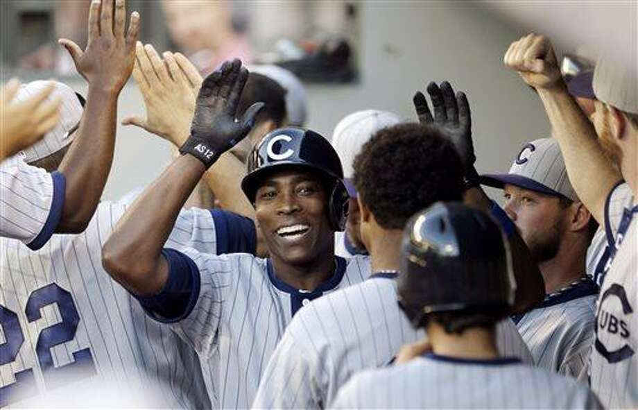 FILE - Chicago Cubs' Alfonso Soriano is congratulated in the dugout on his two-run home run against the Seattle Mariners in the 11th inning of a baseball game in this June 29, 2013 file photo taken in Seattle. Chicago players were upset about the news of teammate Alfonso Soriano's impending trade to the Yankees, and manager Dale Sveum thought that played a part in the Cubs' 3-1 loss to the Arizona Diamondbacks Thursday July 25, 2013. (AP Photo/Elaine Thompson, File) Photo: AP / AP