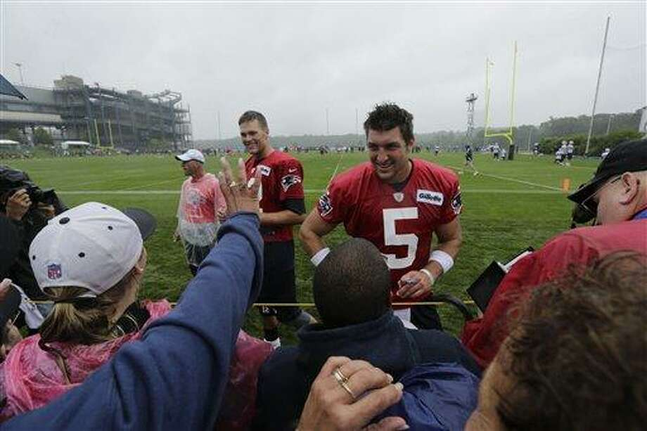 New England Patriots quarterback Tim Tebow signs autographs after an NFL football practice in Foxborough, Mass., Friday, July 26, 2013. At left is Tom Brady. (AP Photo/Charles Krupa) Photo: AP / AP