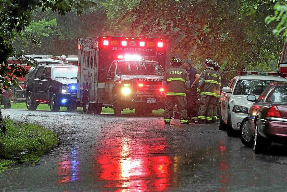 Emergency vehicles and personnel stand near a command post set up for a small plane that crashed on a road just west of Westchester County Airport, Friday, June 13, 2014, in Purchase, N.Y. The single-engine plane took off just after 8 a.m. and went down after hitting some trees, killing Richard Rockefeller, a great grandson of Standard Oil co-founder John D. Rockefeller. (AP Photo/Julie Jacobson) Photo: AP / AP