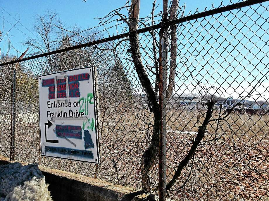 A sign is attached on the fence bordering the property on 100 Franklin St. in Torrington. The property was purchased by the city for $1 last year and will require extensive redevelopment before it can be reused. Photo: Esteban L. Hernandez — The Register Citizen