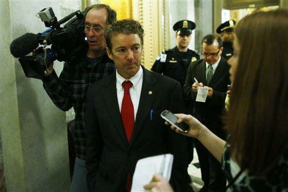 Sen. Rand Paul, R-Ky., is followed by reporters as he walks off the floor of the Senate after his filibuster of the nomination of John Brennan to be CIA director on Capitol Hill in Washington, early Thursday, March 7, 2013. Senate Democrats pushed Wednesday for speedy confirmation of John Brennan's nomination to be CIA director but ran into a snag after Paul began a lengthy speech over the legality of potential drone strikes on U.S. soil. But Paul stalled the chamber to start what he called a filibuster of Brennan's nomination. (AP Photo/Charles Dharapak) Photo: AP / AP