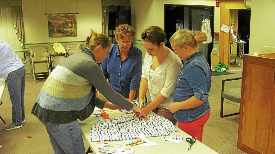 Community members gathered at Northwest Hills Community Church in Torrington Thursday to help sew dresses for African children. Photo: John Nestor — Special To The Register Citizen