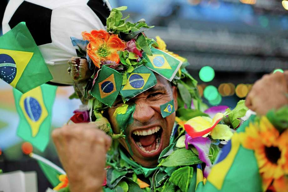 A Brazil soccer fan covered in flowers and his nation's flag cheers inside the FIFA Fan fest area before the start of the World Cup soccer game between Brazil and Croatia on Copacabana beach in Rio de Janeiro, Brazil, Thursday, June 12, 2014. (AP Photo/Silvia Izquierdo) Photo: AP / AP