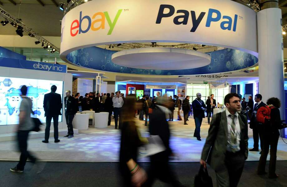 In this  2013 photo, attendees walk in front of an EBay and PayPal display area at the Mobile World Congress, the world's largest mobile phone trade show, in Barcelona, Spain. Photo: Manu Fernandez — The Associated Press  / AP