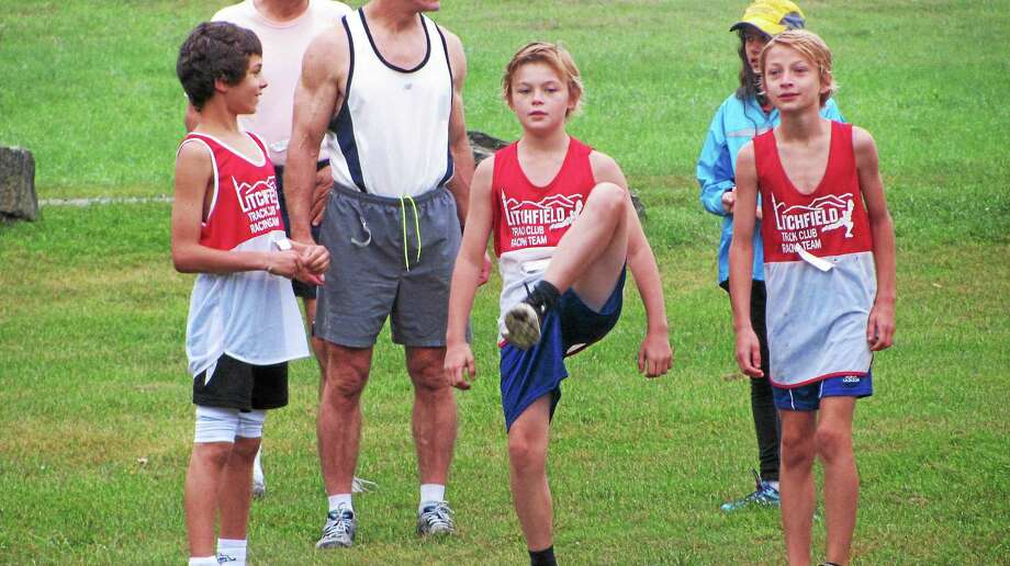 Robin Wright, 11, of Goshen, center, stretches before the 32nd annual Litchfield Cross Country Challenge Saturday. Wright won the race with a time of 21:55. Photo: John Nestor — Special To The Register Citizen