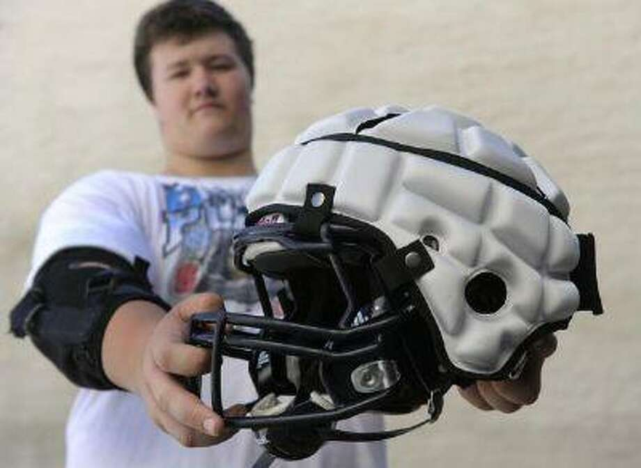 T.J. Callahan, 13, an incoming freshman who plans to play defensive tackle for Columbine, displays the Guardian Cap device that fits over the helmet and reduces impact by as much as 33 percent. Photo: DP / Copyright - 2013 The Denver Post, MediaNews Group.
