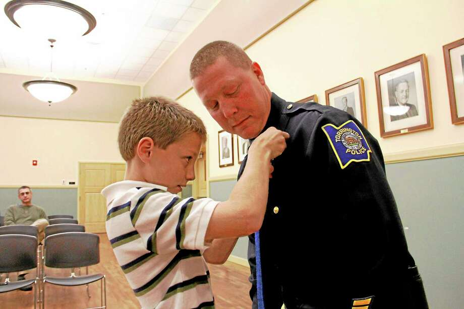 Zachary Barown, 11, pins a new badge on his father, Bart, during a promotion ceremony during the Board of Public Safety on Wednesday at City Hall in Torrington. Photo: Esteban L. Hernandez—Register Citizen