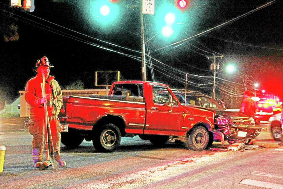 A member of the Torrington Fire Department stands near a two-car accident at the intersection of East Main Street and West Torringford Street on Wednesday night. Photo: Esteban L. Hernandez—Register Citizen
